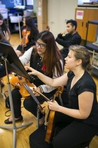Civic Orchestra members work with Schurz High School musicians before a side-by-side performance.