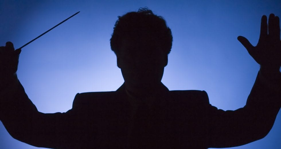 silhouette of the conductor on the blue background